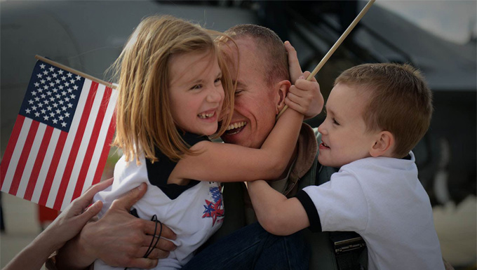 A family welcoming home their dad after a deployment